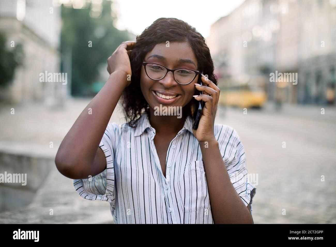 Gros plan portrait d'une femme africaine souriante en lunettes, marchant dans la vieille ville avec un téléphone portable, parlant avec son ami et souriant à l'appareil photo. Personnes Banque D'Images