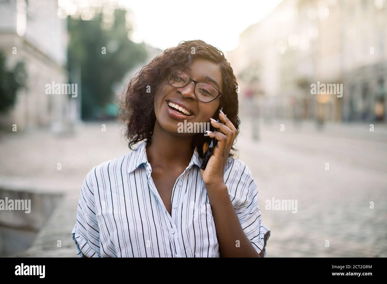 Gros plan portrait d'une jolie fille africaine en boucles parlant sur un téléphone mobile, regardant l'appareil photo et riant, marchant à l'extérieur sur la vieille ville rue à Banque D'Images