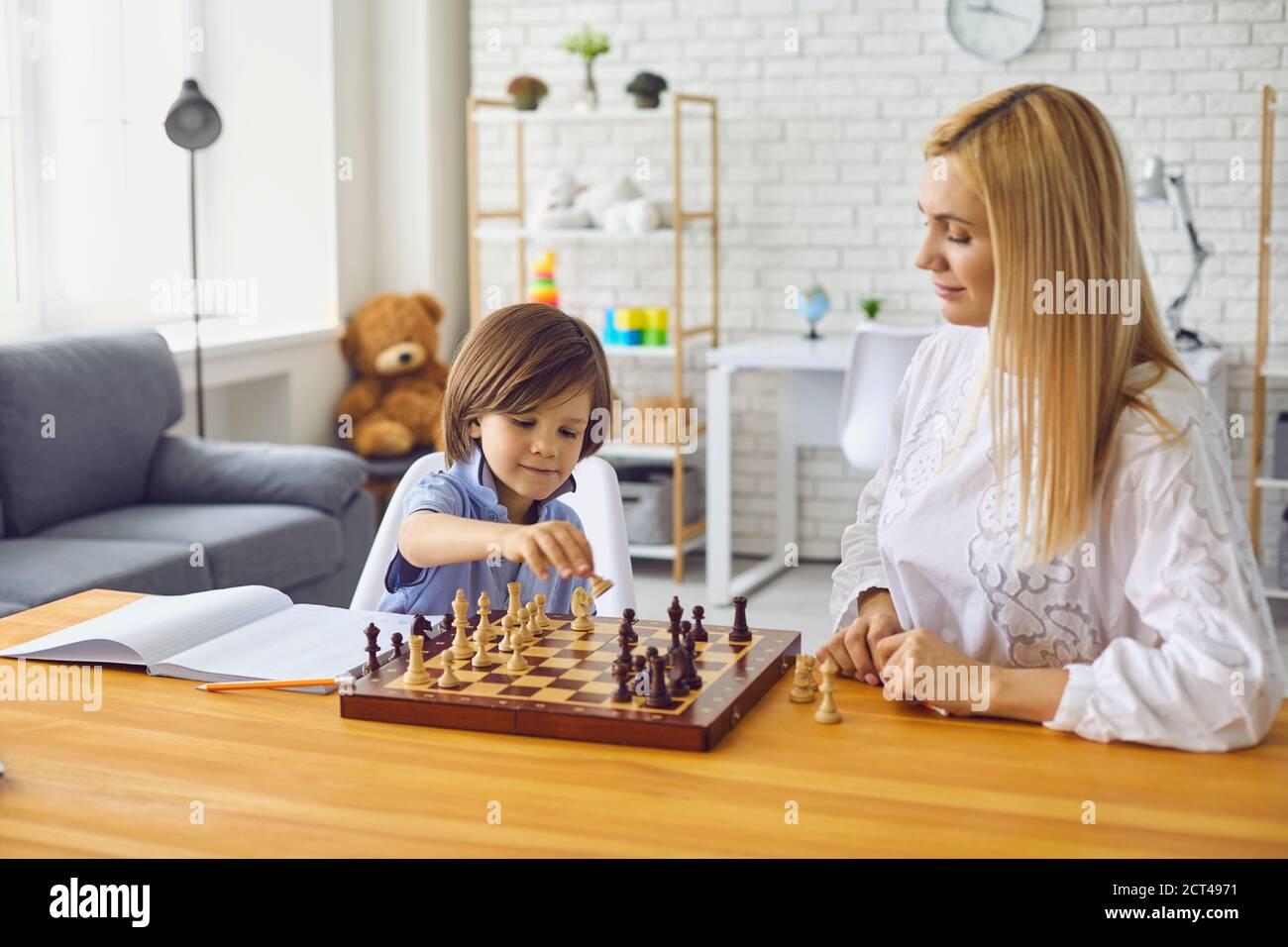 Mère et fils jouent aux échecs à la table à la maison.Happy famille avec parents et enfants jouant à un jeu de société à la maison Banque D'Images