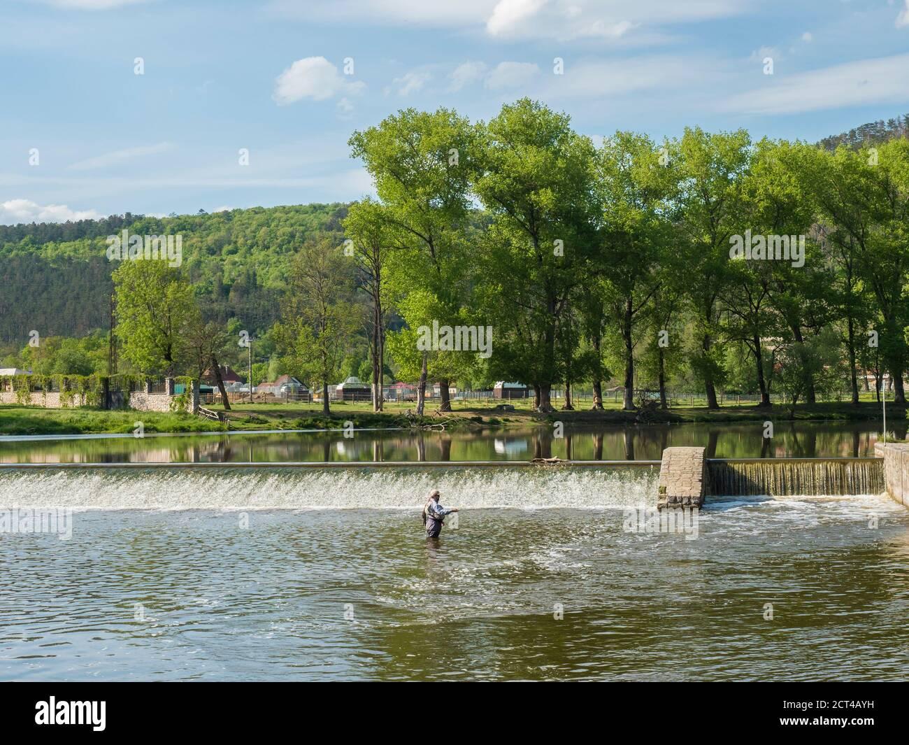 Weir sur la rivière Berounka dans le village de Zadni Treban avec pêcheur à la mouche debout dans le ruisseau et arbres verts luxuriants. Jour d'été ensoleillé, République tchèque Banque D'Images