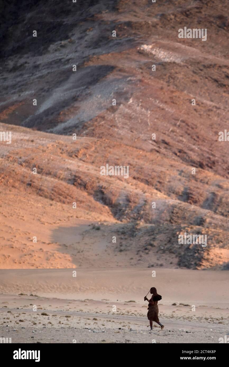 Une femme Himba marche dans la région aride qui entoure sa maison dans la région de Kunene en Namibie. Banque D'Images
