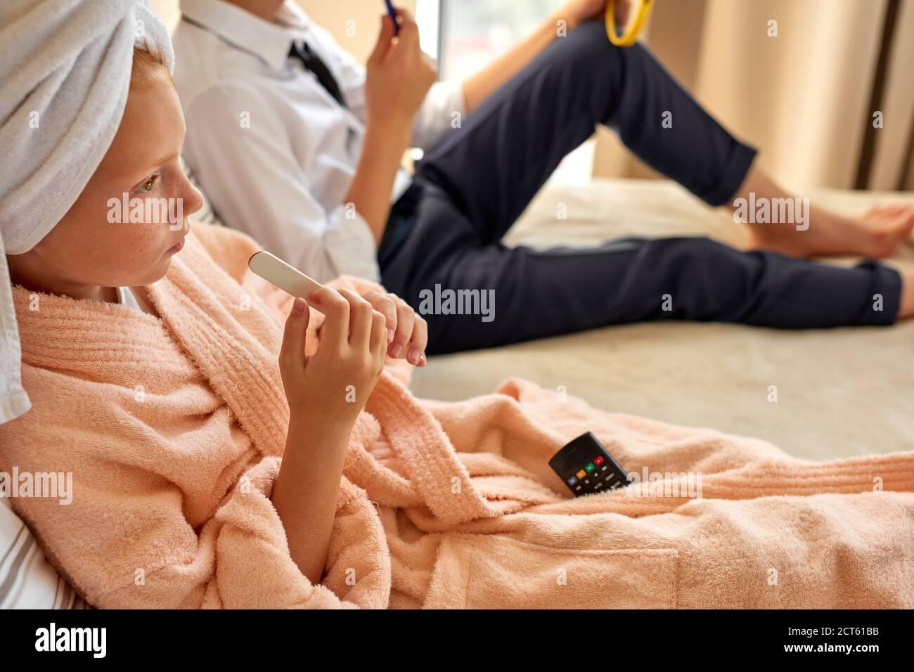 beau couple d'enfants commence la journée ensemble, fille et garçon se reposent sur le lit, repos Banque D'Images