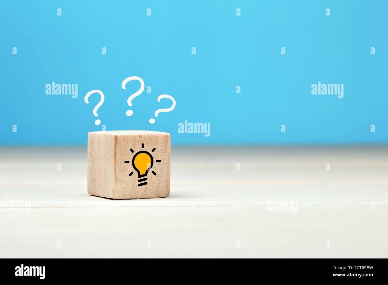 Concept créatif d'idée, de solution ou de résolution de problèmes. Point d'interrogation et icônes d'ampoule sur un cube en bois sur fond bleu. Banque D'Images