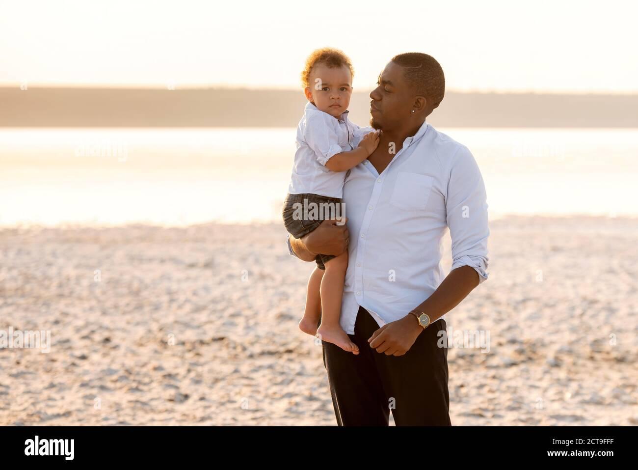 Portrait du jeune père et du petit-fils sérieux. Bébé garçon sur les mains du père Banque D'Images