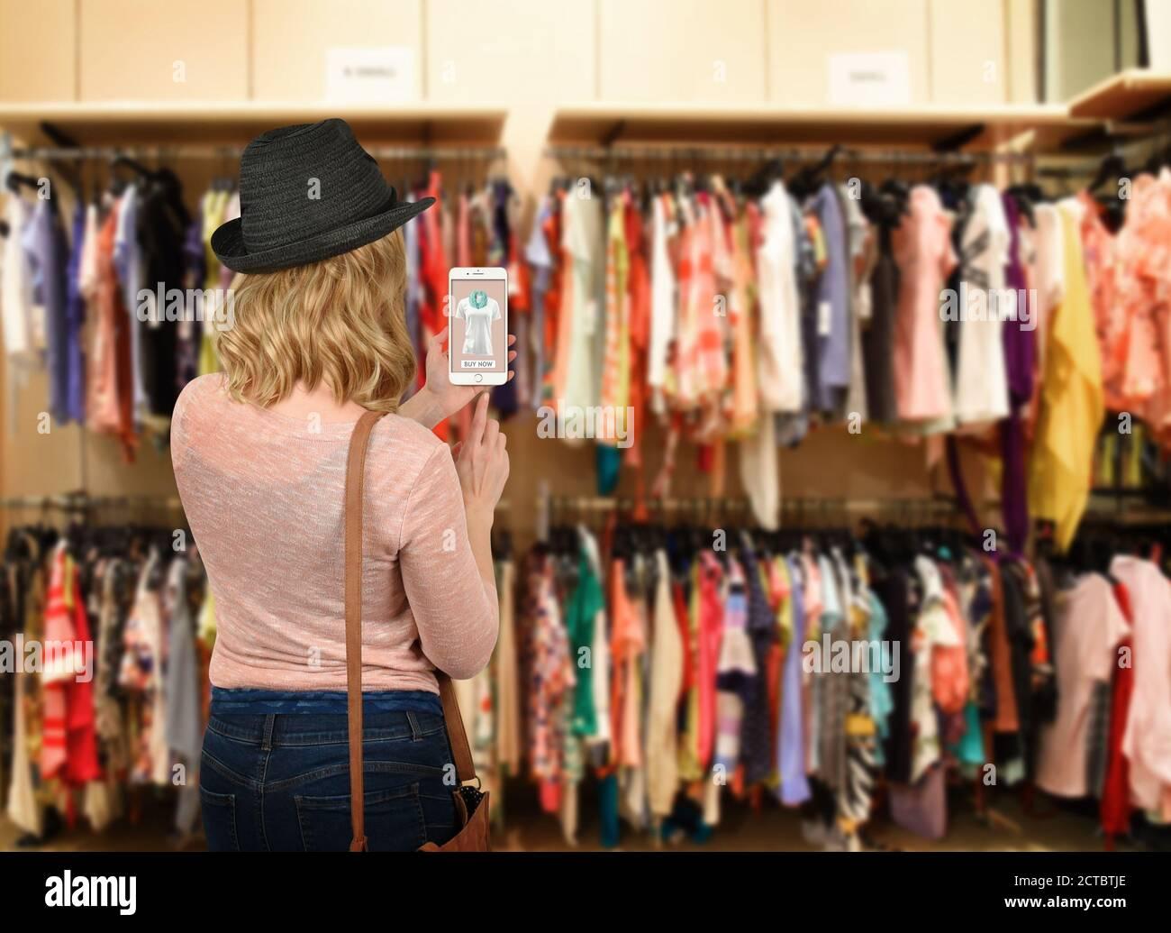 Une femme est dans un magasin de vêtements tenant un téléphone portable cherchant à acheter une chemise en ligne dans un application pour un concept de shopping ou de mode sur la technologie Banque D'Images