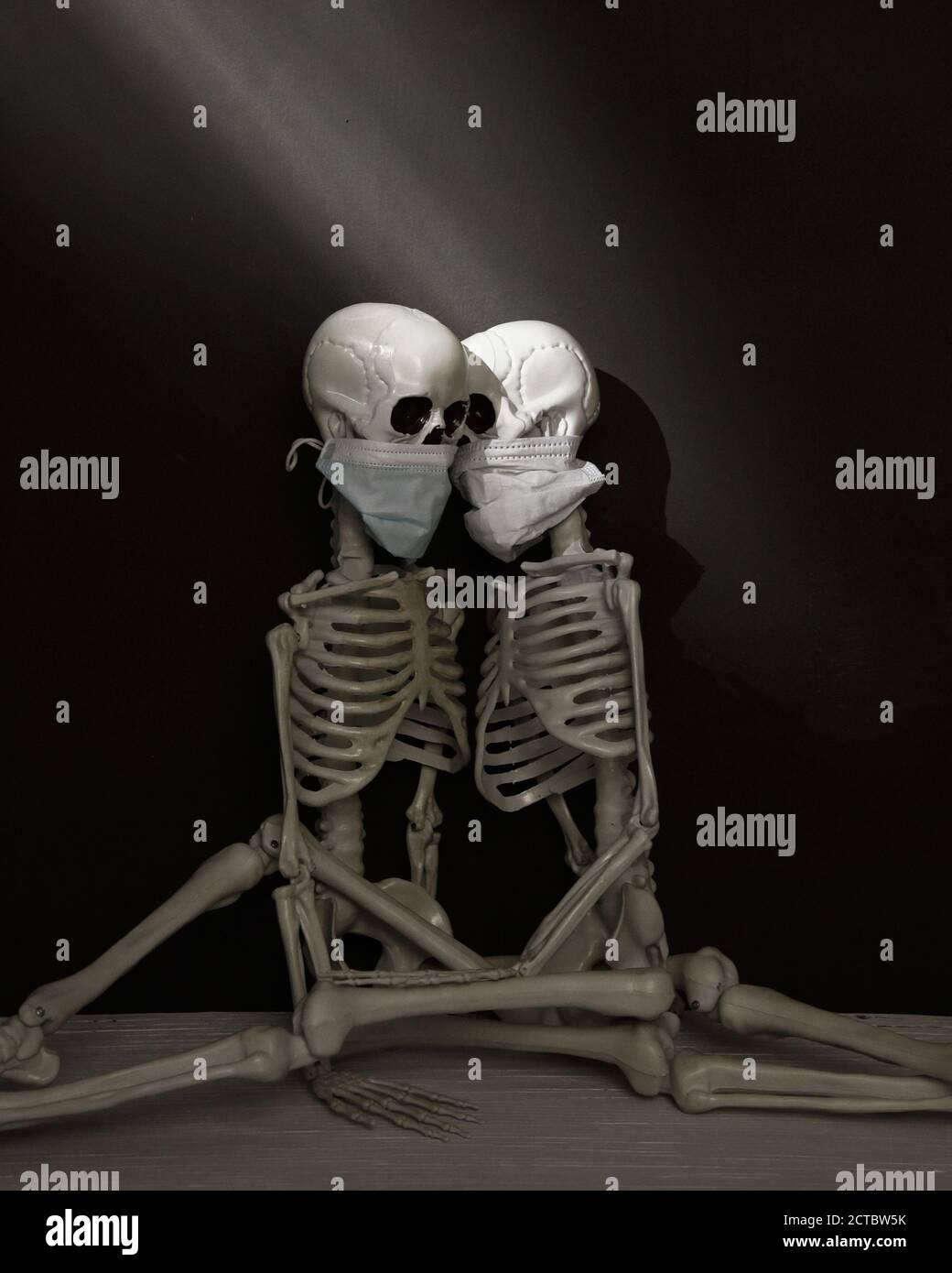 Deux squelettes humains sont assis ensemble dans une pièce sombre portant des masques pour un étrange concept de santé du virus pandémique. Banque D'Images