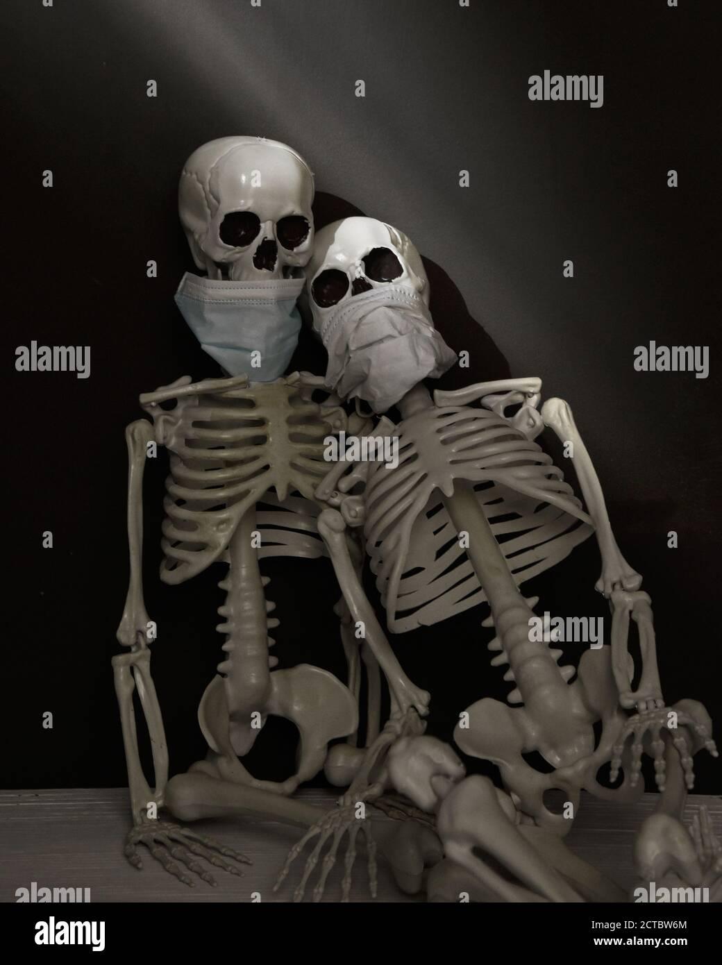 Deux squelettes portent des masques faciaux contre un mur noir avec la lumière du soleil pour un étrange concept de décoration d'halloween effrayant. Banque D'Images