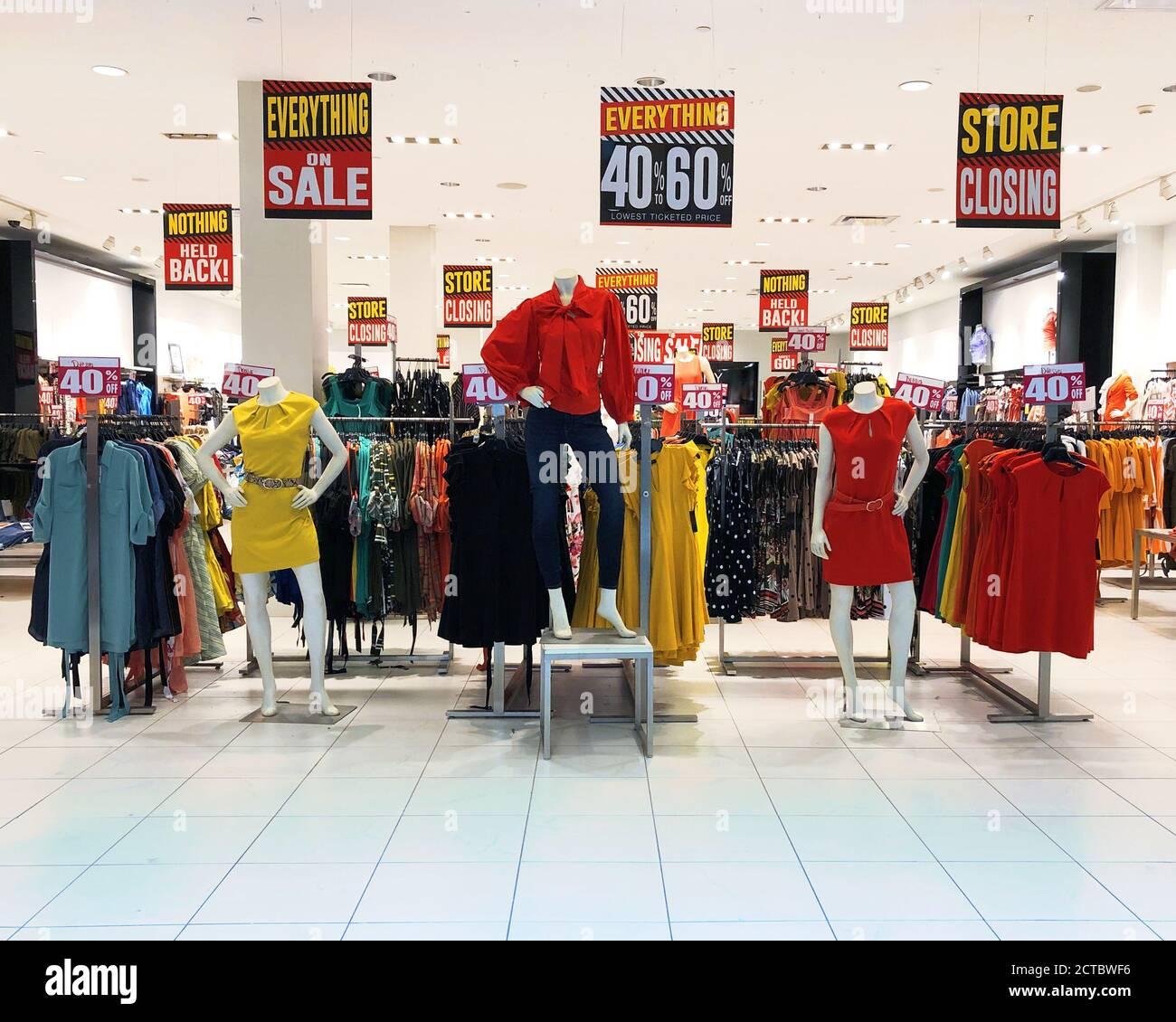 Un centre commercial de magasins a plusieurs robes et vêtements de mode pour femmes en vente avec des panneaux de fermeture de magasin pour un concept de pandémie au sujet des entreprises en faillite. Banque D'Images