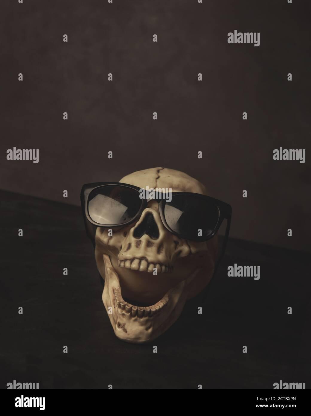 Une tête de crâne de skelton effrayante rie avec des lunettes de soleil noires sur pour un concept de peur. Banque D'Images