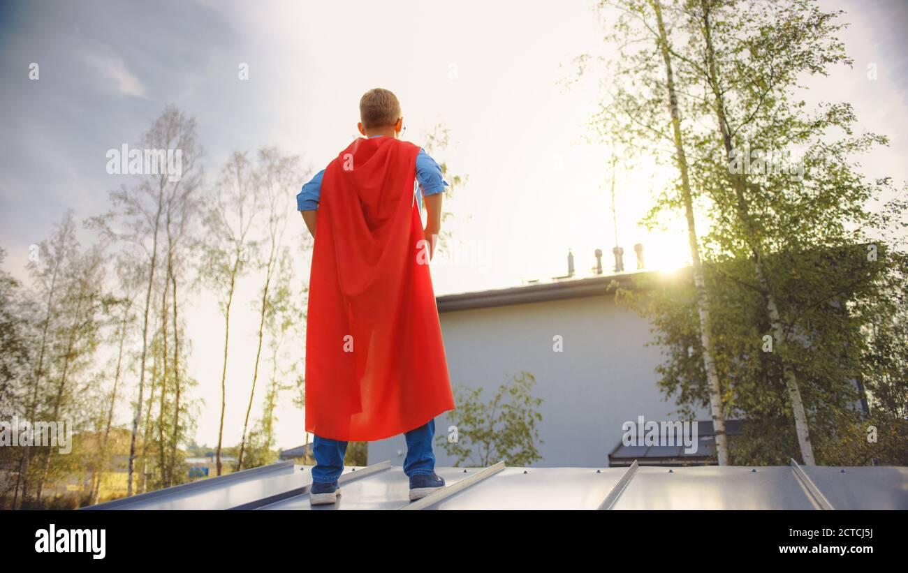 Garçon joue un rôle de Super Hero. Il est debout sur le toit d'une maison avec ses mains à la taille. Le jeune homme porte une cape rouge vif. Il l'est Banque D'Images