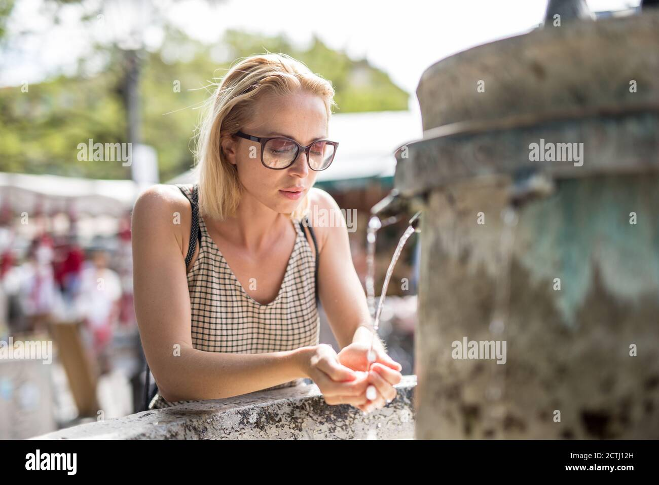 Soif jeune femme cucasie décontractée de boire de l'eau de la ville publique fontaine par une chaude journée d'été Banque D'Images