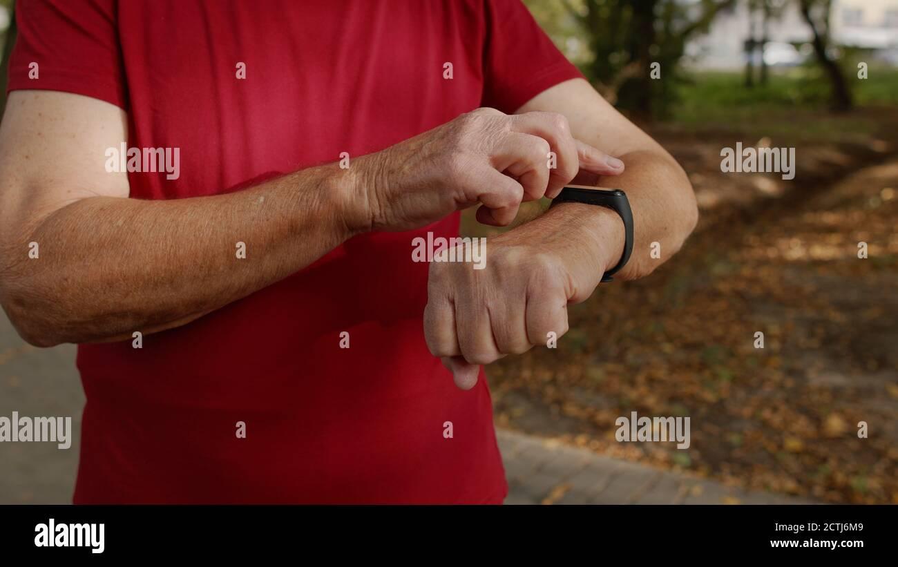 Ancien coureur débutant à toucher l'écran tactile de la montre intelligente, suivi de la distance, contrôle du pouls pendant l'entraînement physique. Moniteur de fréquence cardiaque avant le jogging. Concept de mode de vie sain Banque D'Images
