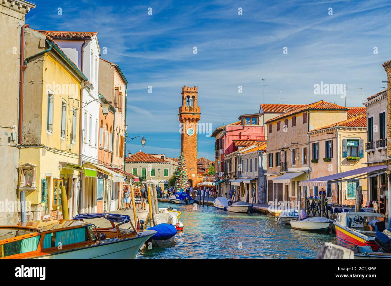 Îles de Murano avec tour d'horloge Torre dell'Orologio, bateaux et bateaux à moteur dans le canal d'eau, bâtiments traditionnels colorés, lagune vénitienne, région de Vénétie, Italie du Nord. Carte postale de Murano. Banque D'Images