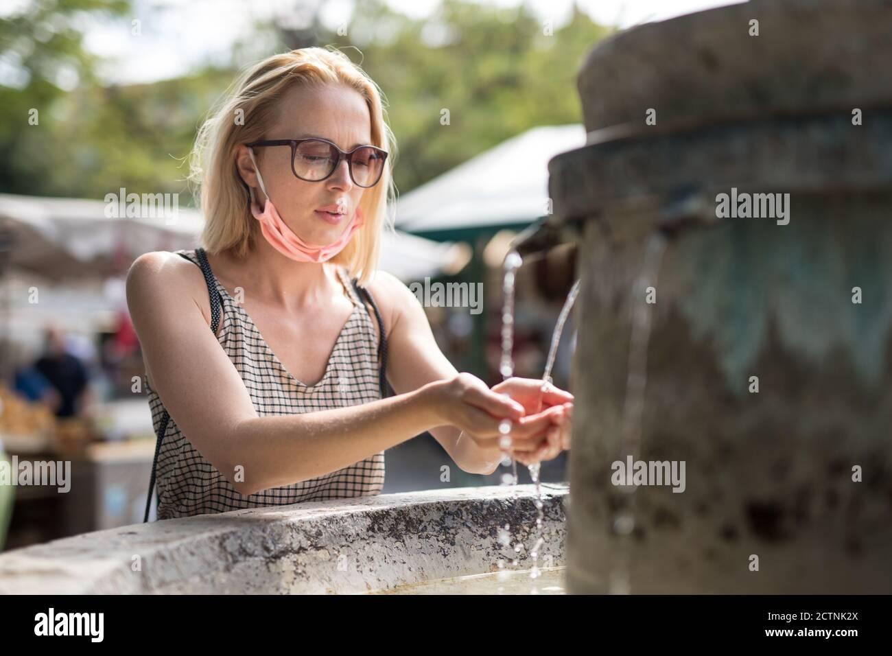 Une jeune femme cucasienne décontractée assoiffée portant un masque médical pour boire de l'eau de la fontaine publique de la ville par une chaude journée d'été. Nouvelle vie pendant le covid Banque D'Images