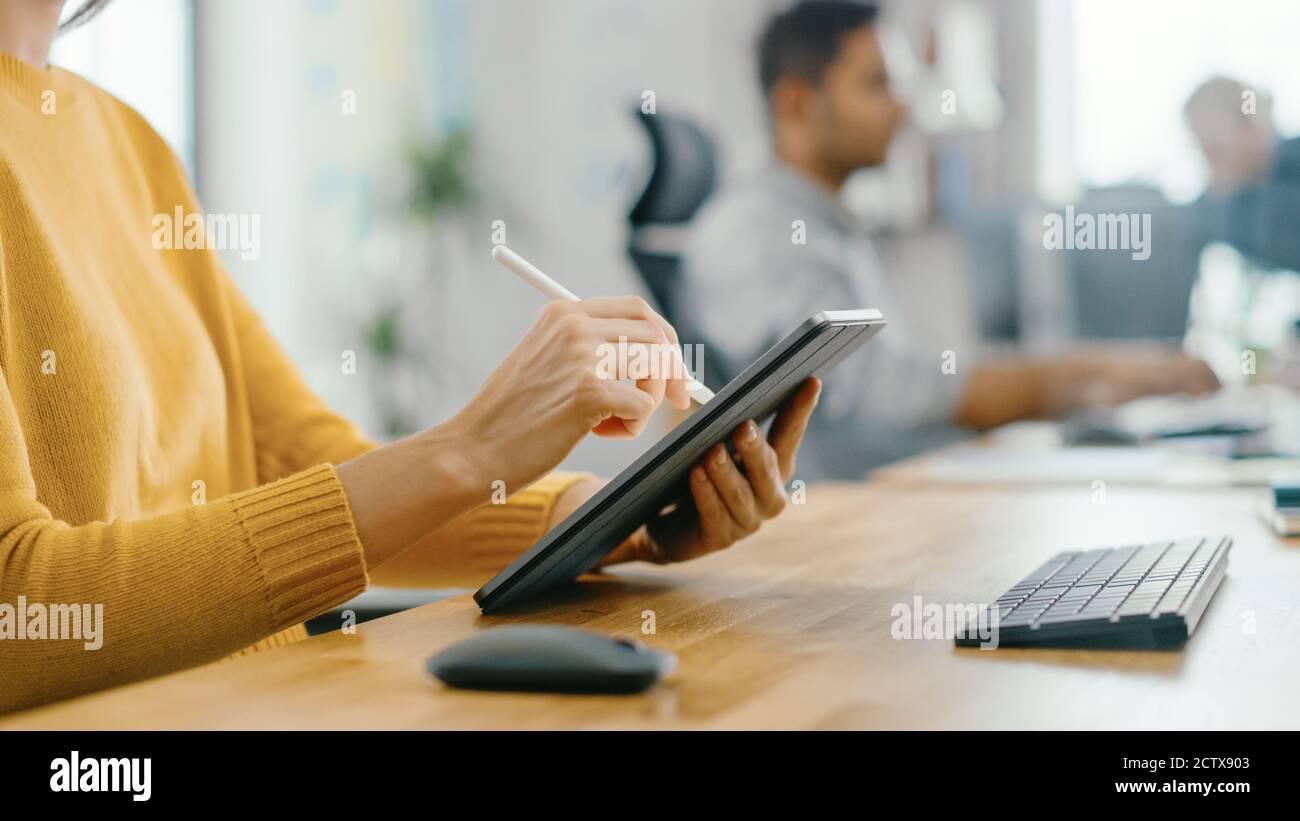 Anonyme jeune femme assise à son bureau elle est dessin, écriture et utilisation de stylo avec ordinateur de tablette numérique. Concentrez-vous sur vos mains avec le stylet. Bureau lumineux Banque D'Images