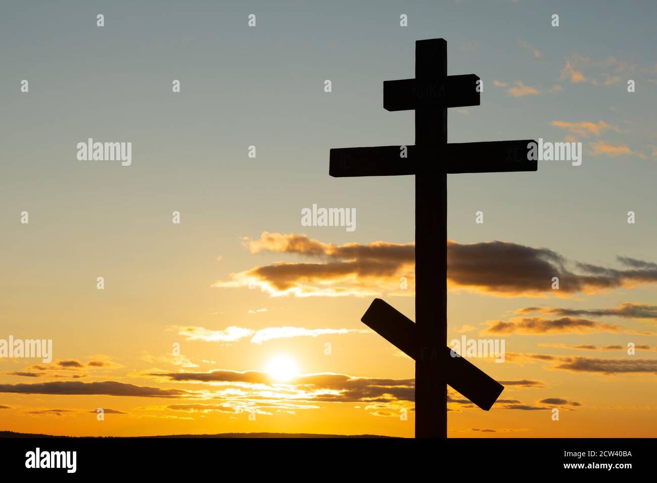 Les orthodoxes se croisent dans les rayons de soleil du coucher du soleil. Foi et concept de foi. Moment spirituel Banque D'Images