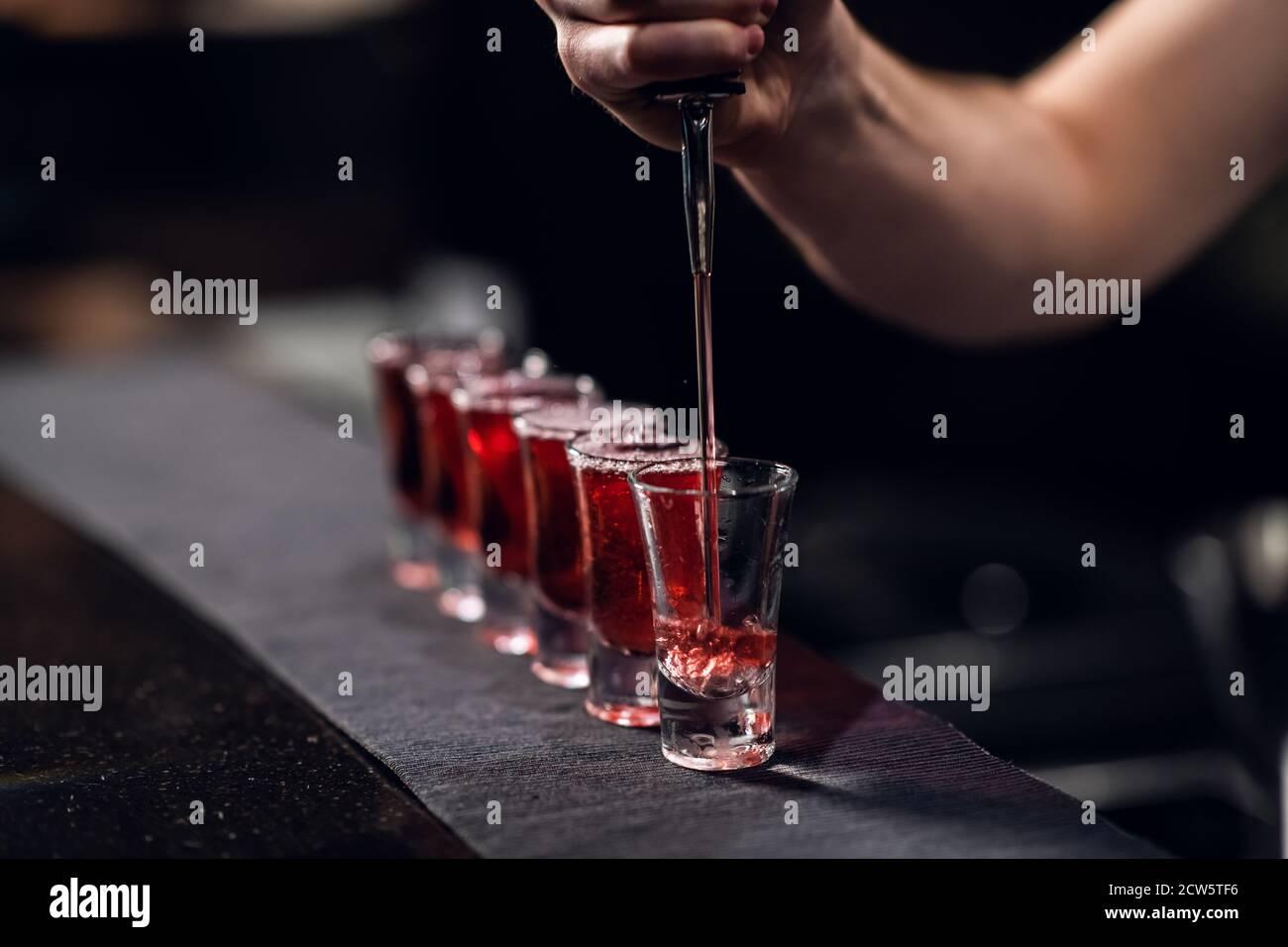 le barman remplit les prises de vue avec de la liqueur rouge provenant d'une bouteille sur le bar. Banque D'Images