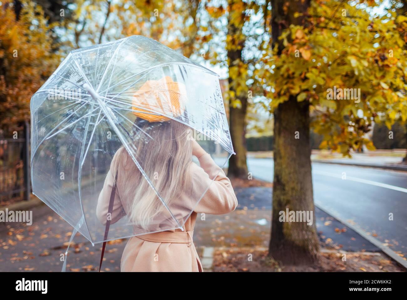 Une femme à la mode en vêtements d'automne marche à l'extérieur sous un parapluie transparent sous la pluie. Météo d'automne. Banque D'Images