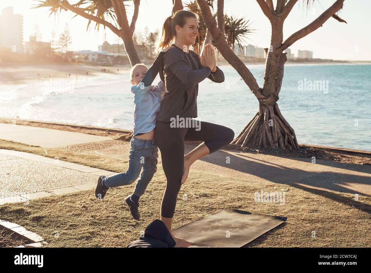 Jeune mère et fils faisant de la gymnastique et s'étirant dans le parc de la ville sur le soleil avec vue sur l'océan. Femme en yoga asana et garçon sur ses épaules Banque D'Images