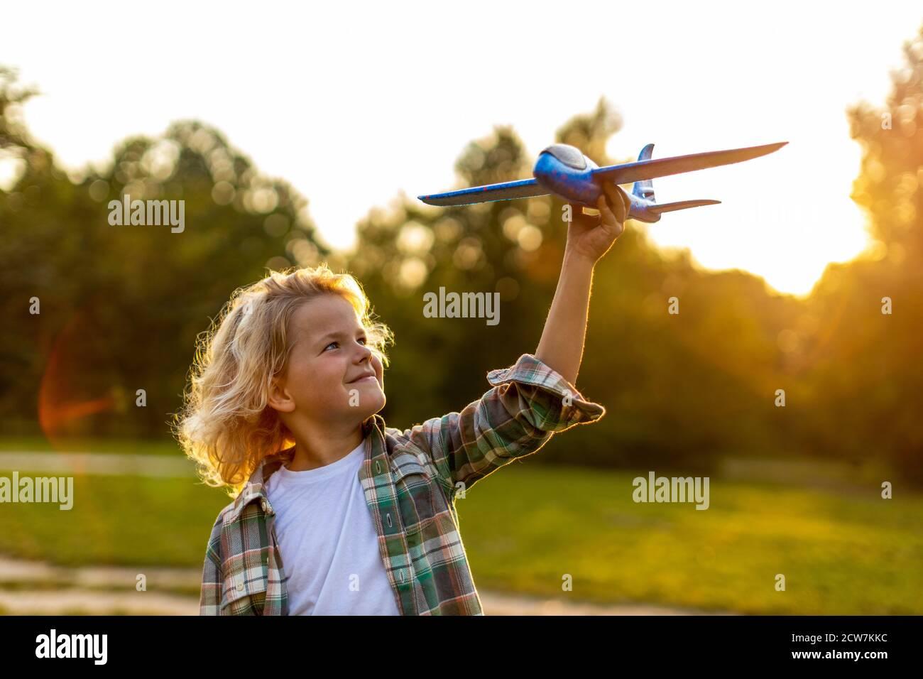 Petit garçon jouant avec l'avion jouet dans le parc Banque D'Images