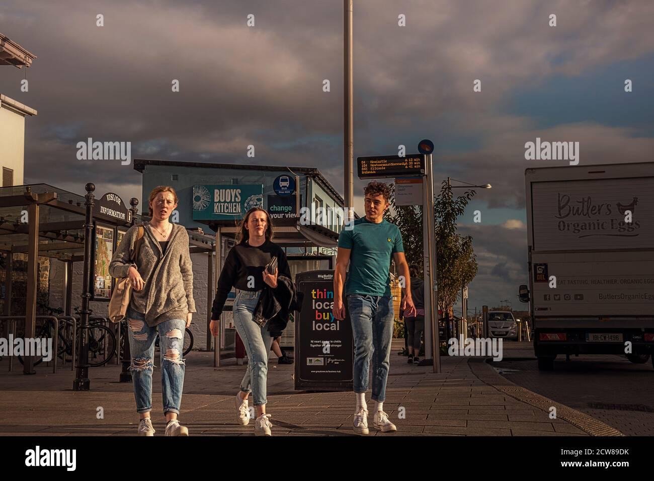 La vie quotidienne. Les filles et l'homme marchant vers l'appareil photo dans la rue principale autour de la gare. Greystones. Irlande. Banque D'Images