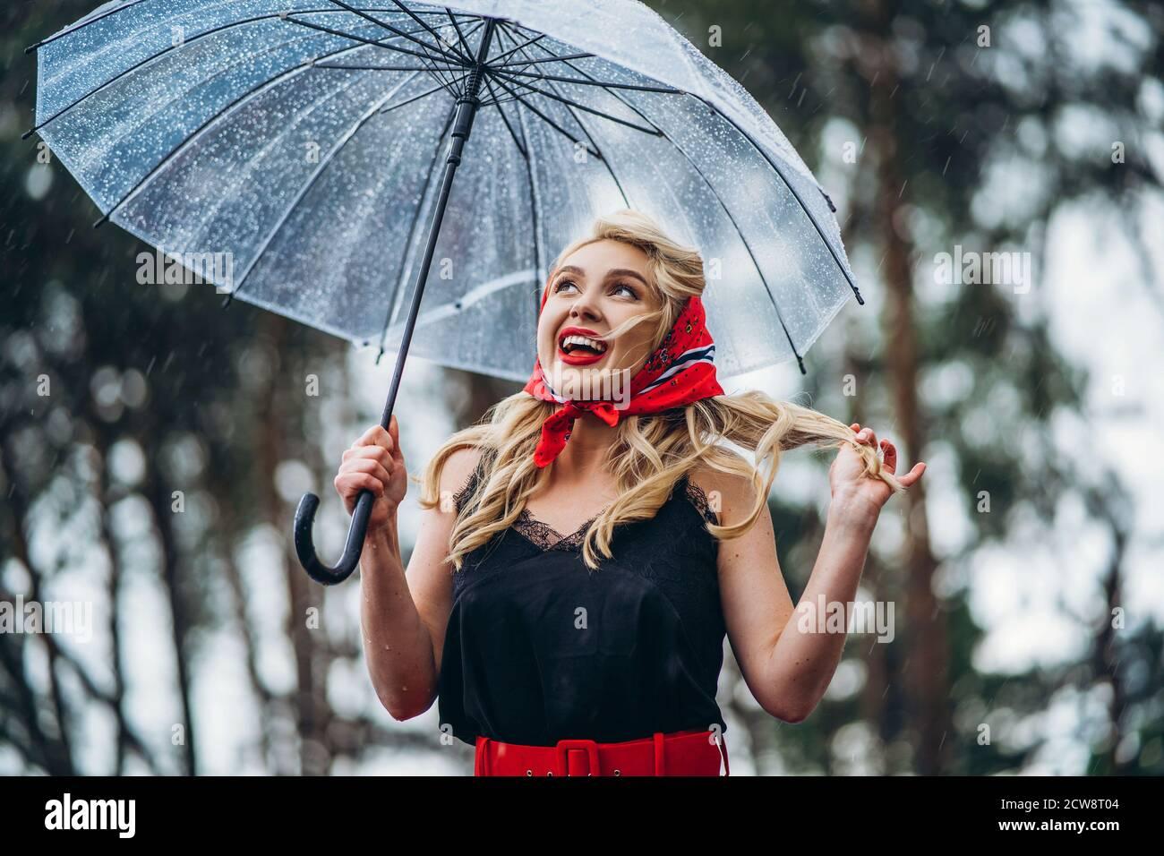 Joyeux blond stylé avec des lèvres rouges qui marchent jour de pluie à l'extérieur avec parapluie transparent Banque D'Images