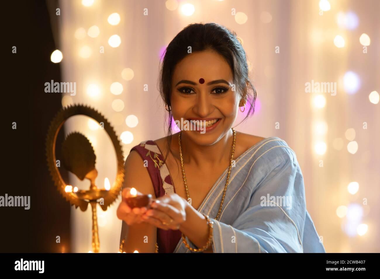 Femme souriant tout en tenant une diya pour allumer une lampe À l'occasion de Diwali Banque D'Images