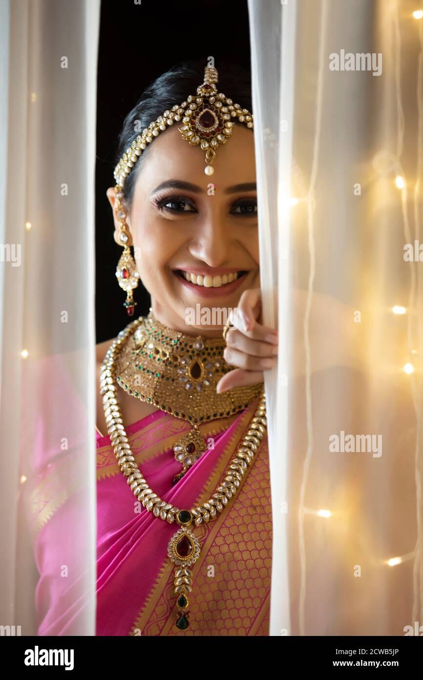 Une femme en tenue ethnique souriante a pensé le rideau Banque D'Images