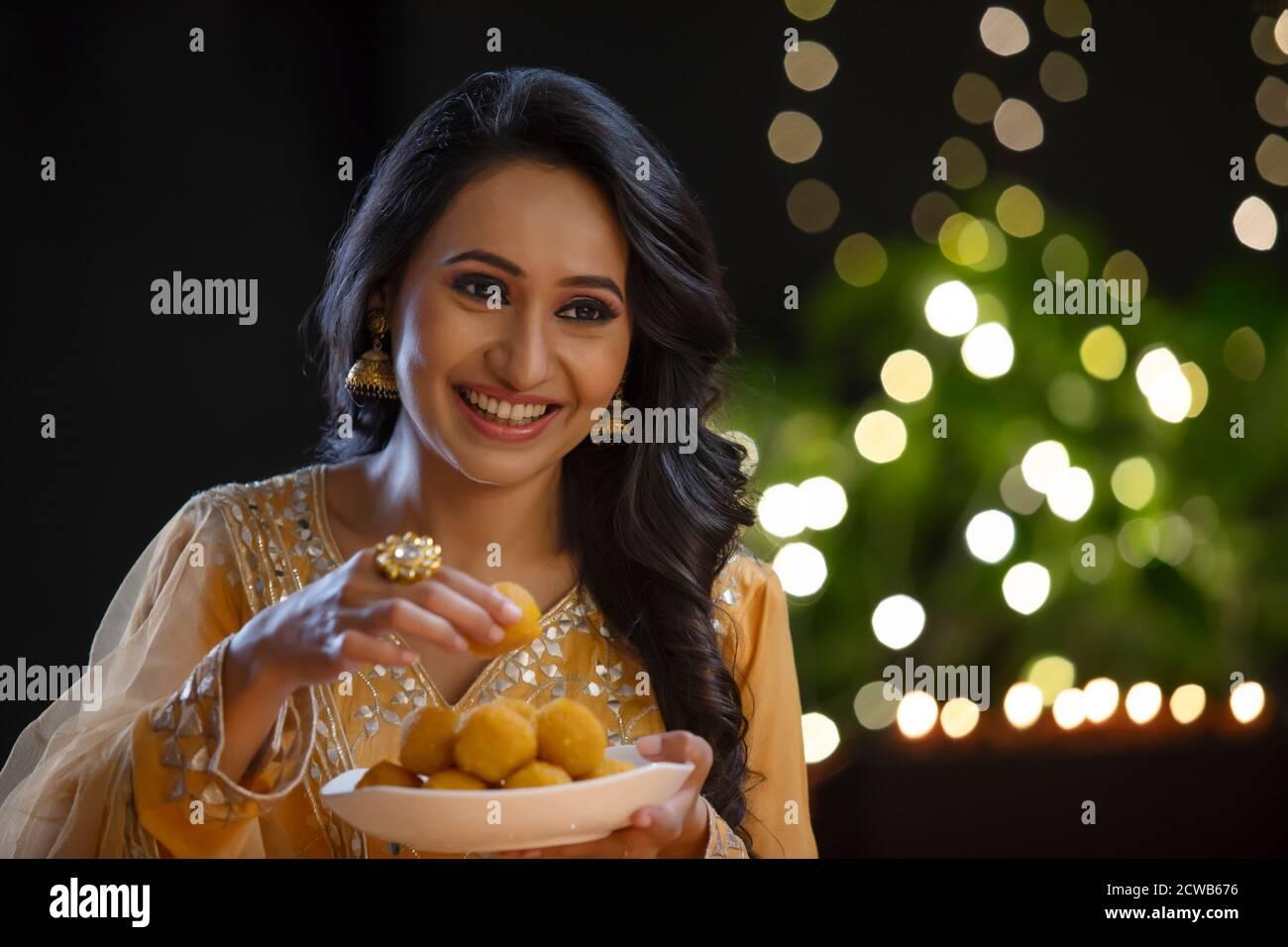 Femme cueillant une ladoo dans une assiette avec un sourire Banque D'Images