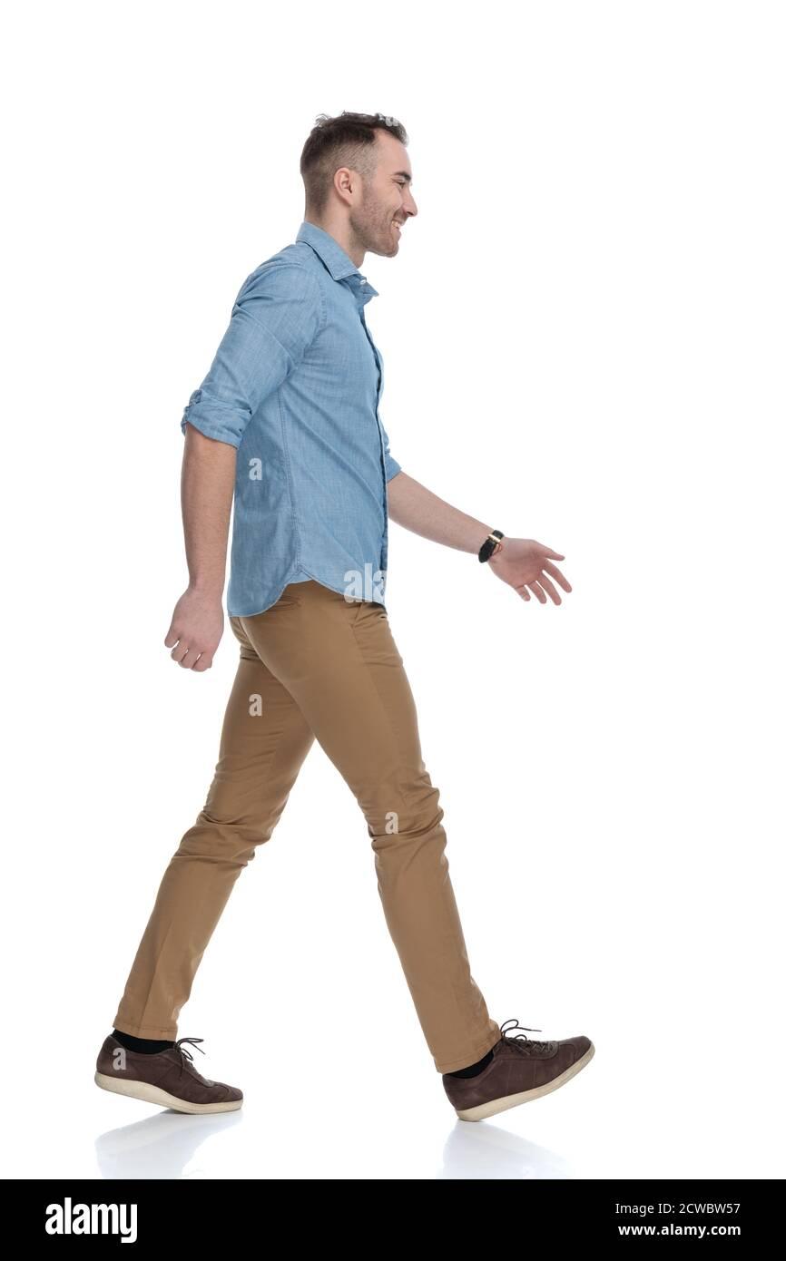 Vue latérale d'un homme heureux et décontracté qui rit et porte une chemise bleue, qui marche sur fond blanc de studio Banque D'Images