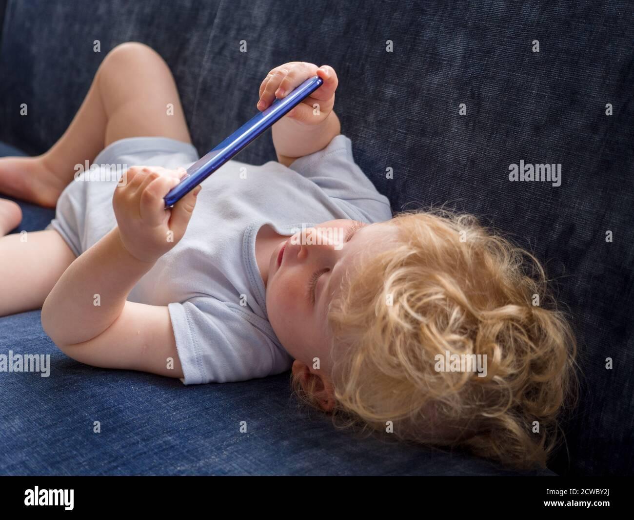Bébé d'un an regardant des vidéos youtube sur un mobile téléphone Banque D'Images