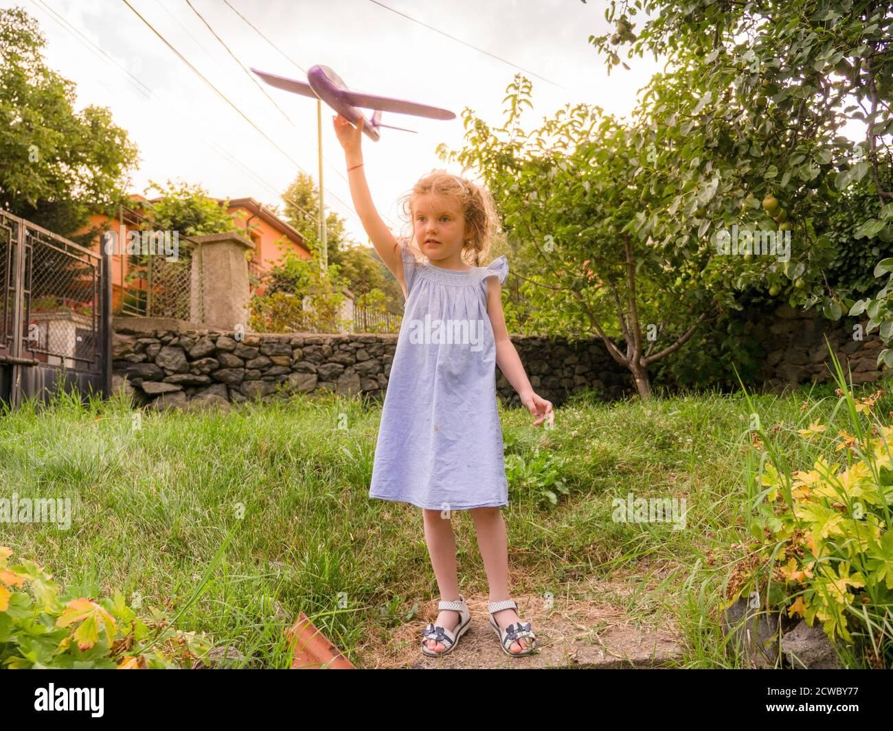 Bonne jeune fille volant jouet avion à l'extérieur dans le jardin Banque D'Images