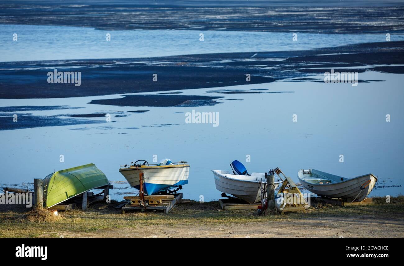 Petits bateaux à rames stockés à la plage en faisant fondre le lac au printemps, en Finlande Banque D'Images