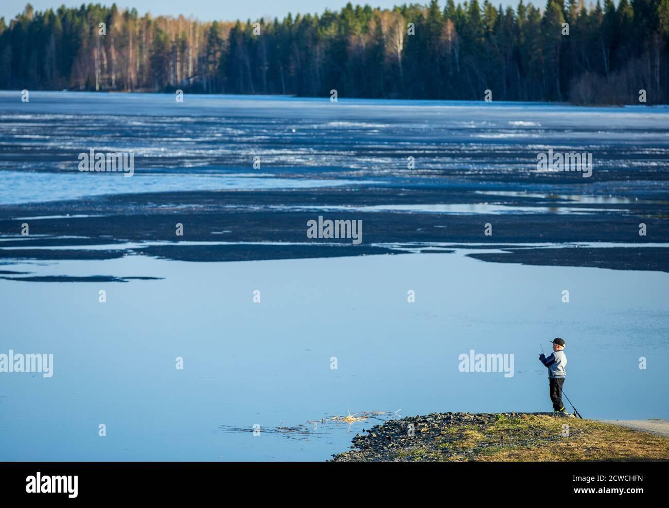 Jeune garçon pêchant seul sur la plage d'un lac à moitié gelé à Spring, en Finlande Banque D'Images