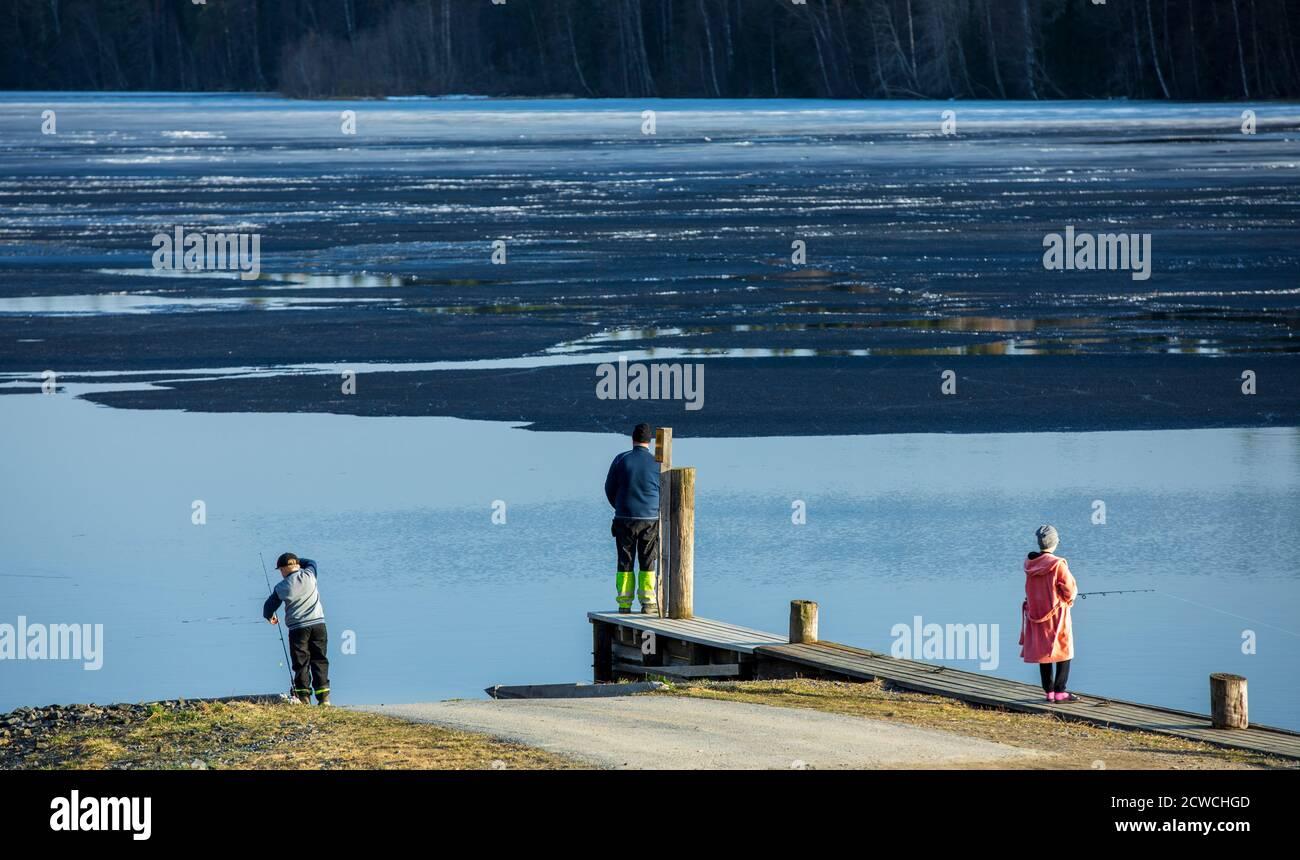 Pêche familiale avec des tiges de filature de la plage d'un lac à moitié gelé à Spring, Finlande Banque D'Images