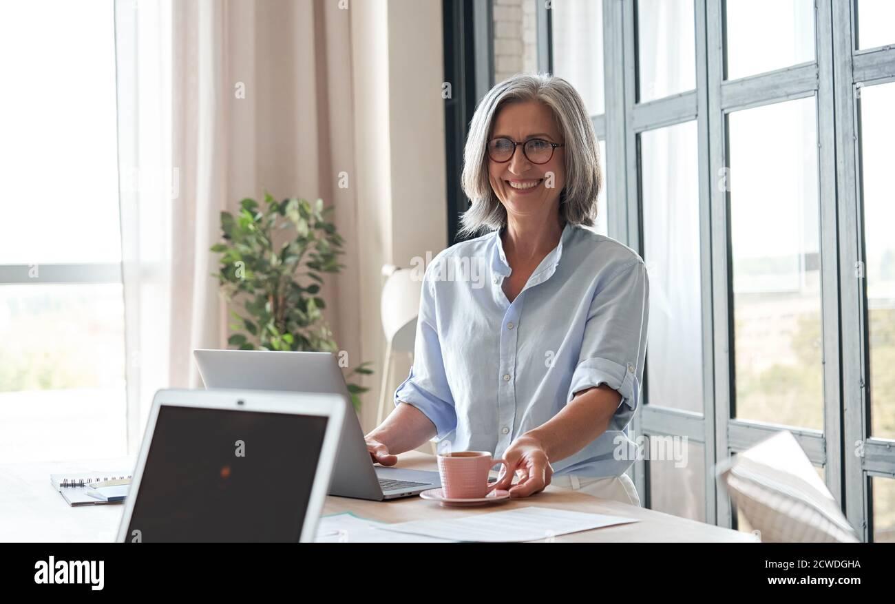 Bonne vieille femme mentor, coach ou enseignante debout à table pendant l'atelier. Banque D'Images