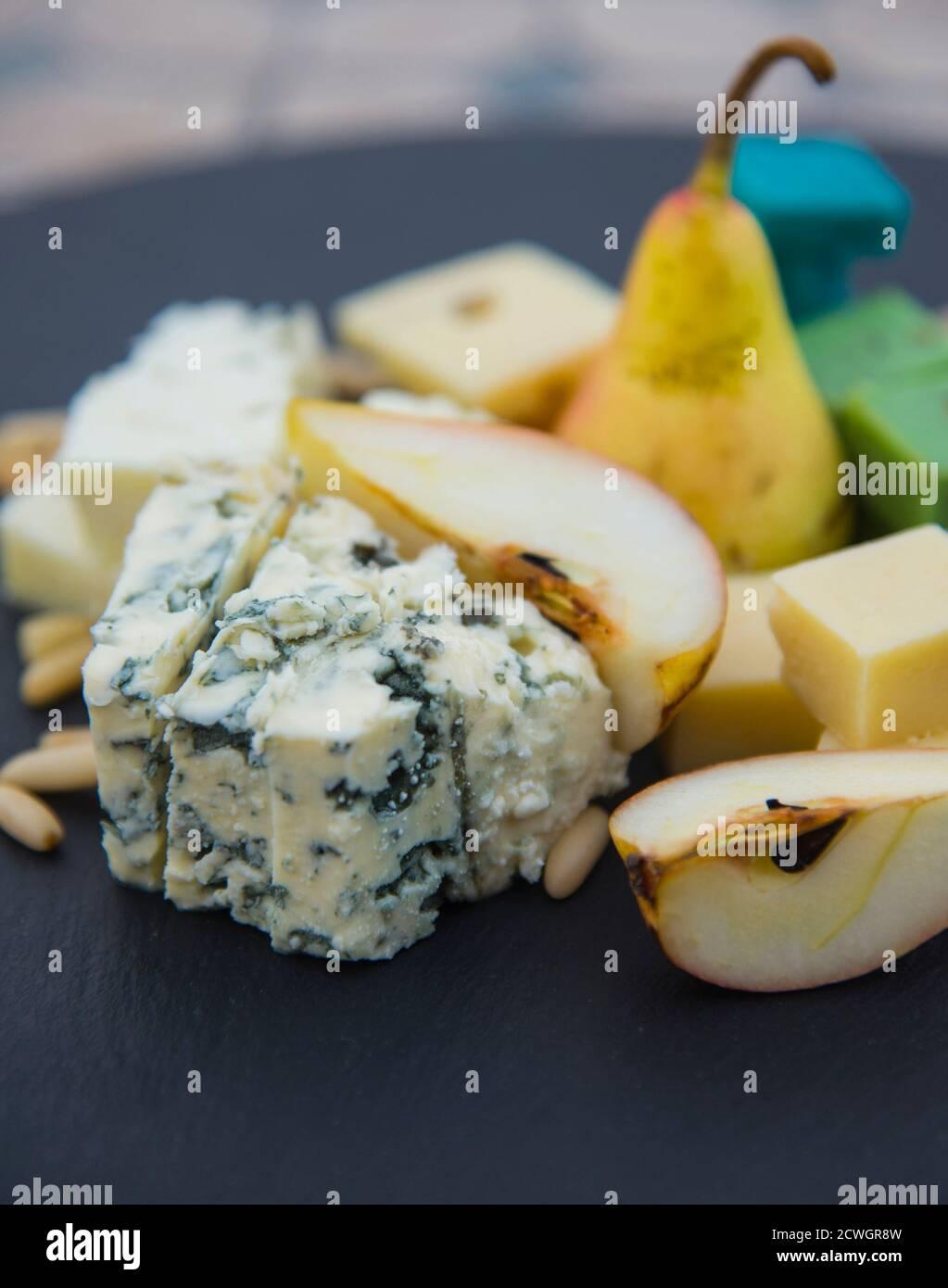 Morceaux de différents fromages, poires mûres et noix de pin. Produit laitier sur l'assiette noire Banque D'Images