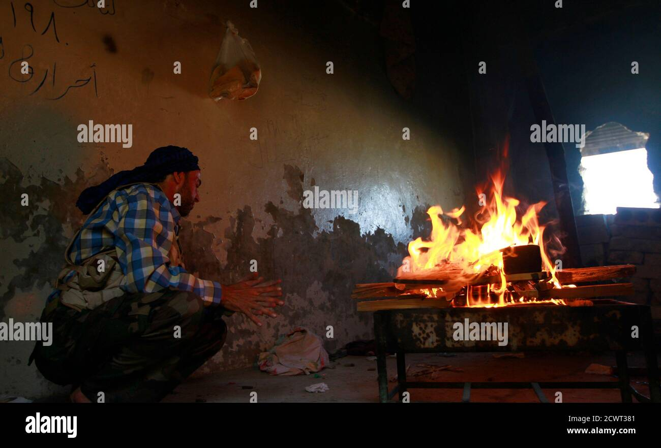 A member of the Free Syrian Army sits near a fire to prepare food near Nairab military airport, in Aleppo June 27, 2013. REUTERS/Hamid Khatib (SYRIA - Tags: CONFLICT) Banque D'Images