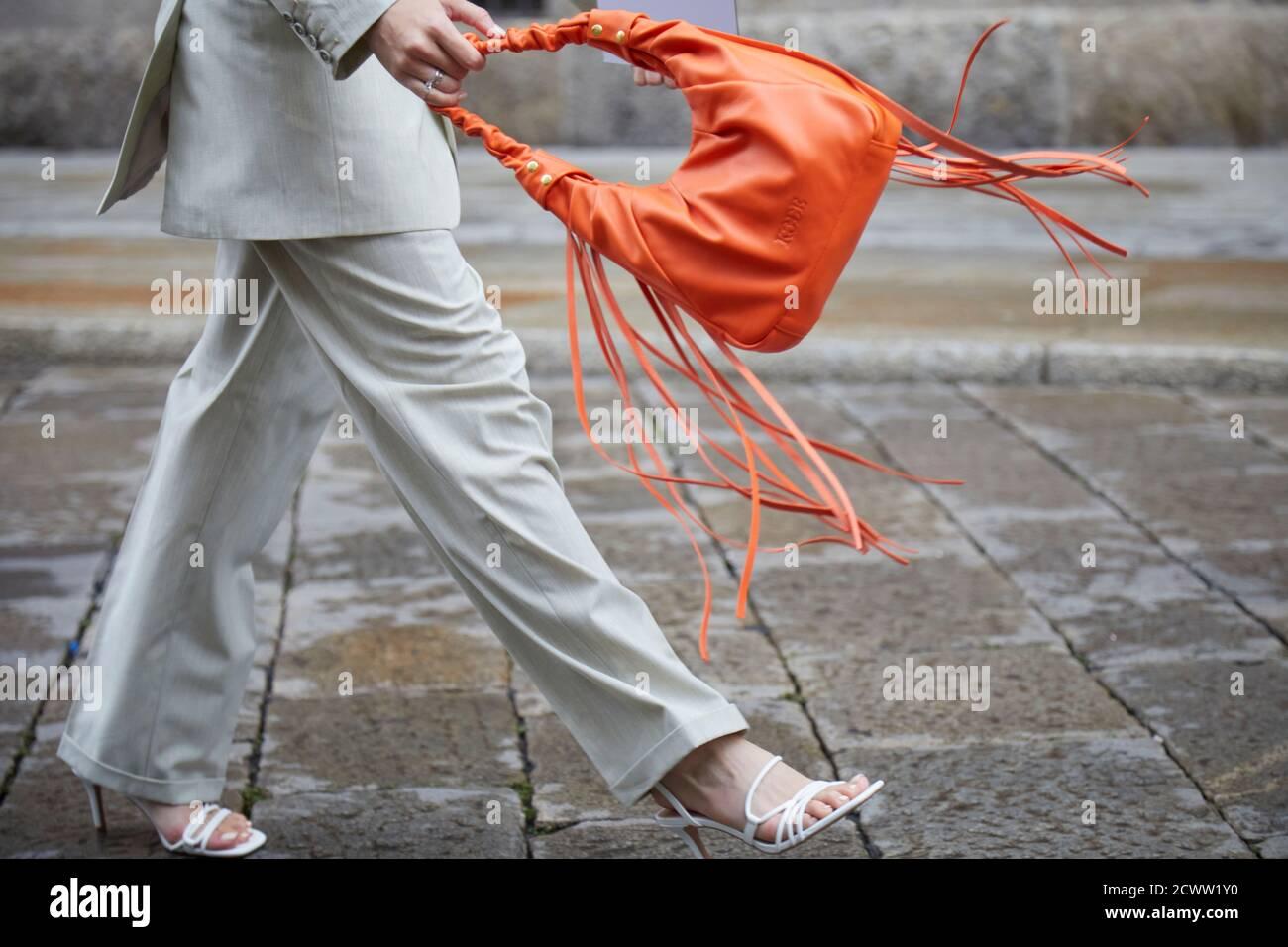 MILAN, ITALIE - 24 SEPTEMBRE 2020: Femme marchant avec sac en cuir orange avec franges avant le spectacle de mode Max Mara, Milan Fashion week Street style Banque D'Images