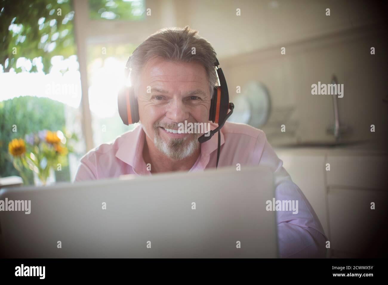 Portrait souriant homme senior avec casque travaillant sur ordinateur portable Banque D'Images