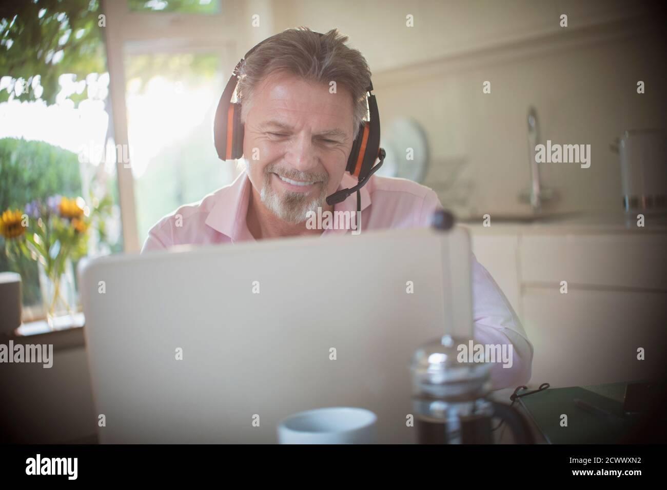 Homme senior heureux avec des écouteurs qui travaillent sur un ordinateur portable le matin cuisine Banque D'Images