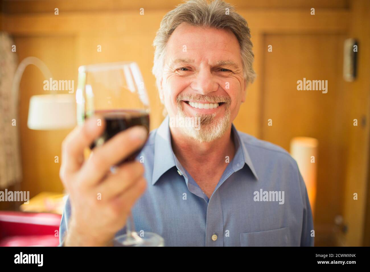 Portrait heureux insouciant homme senior buvant du vin rouge Banque D'Images
