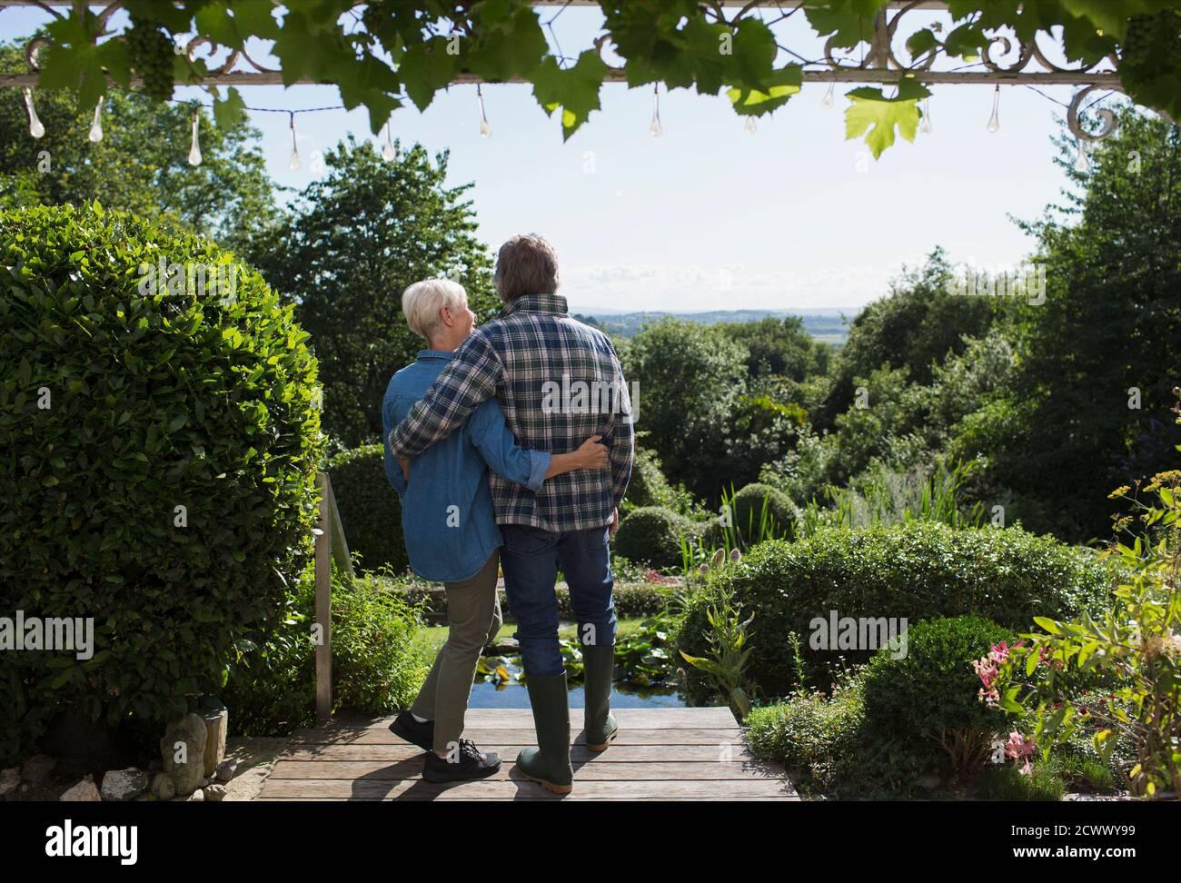 Un couple affectueux qui s'enserre dans un jardin d'été ensoleillé Banque D'Images