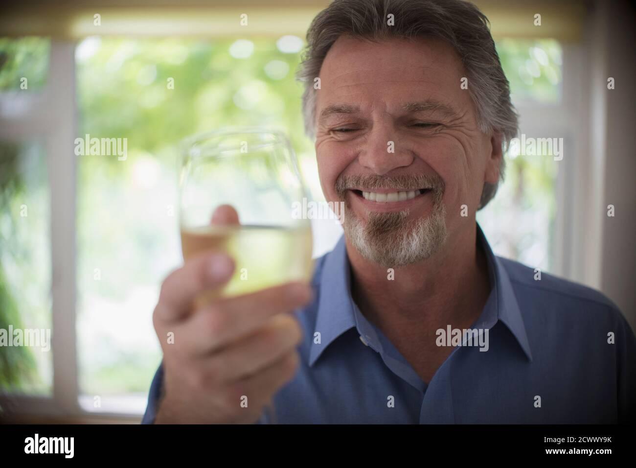 Gros plan homme souriant et expérimenté qui boit du vin blanc Banque D'Images