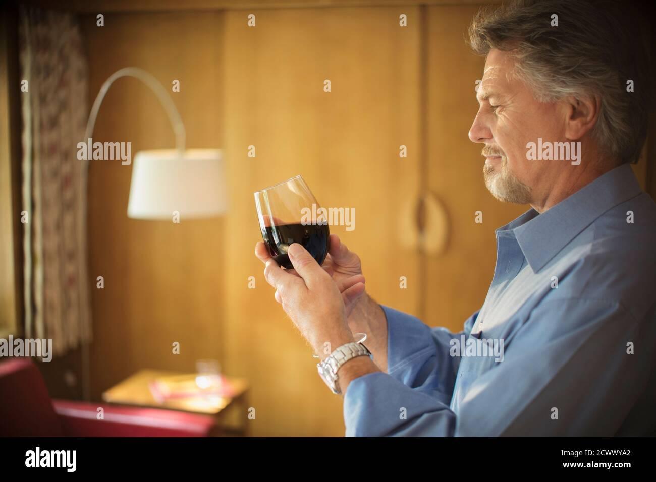Un homme expérimenté goûtant du vin rouge dans le salon Banque D'Images
