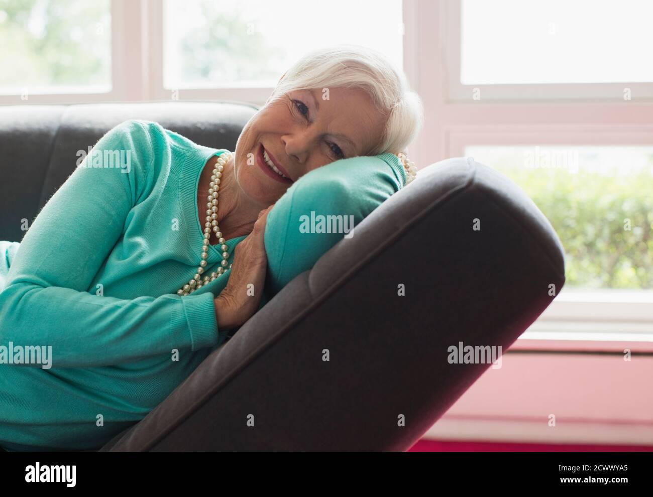 Portrait bonne femme sénior se détendant sur une chaise longue Banque D'Images