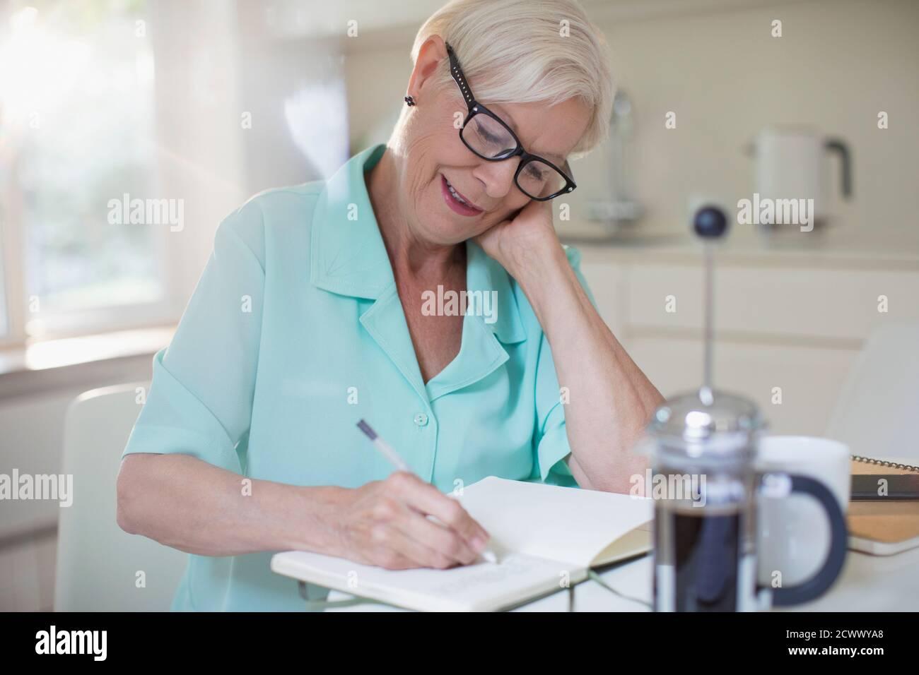 Femme âgée écrivant dans le journal dans la cuisine du matin Banque D'Images