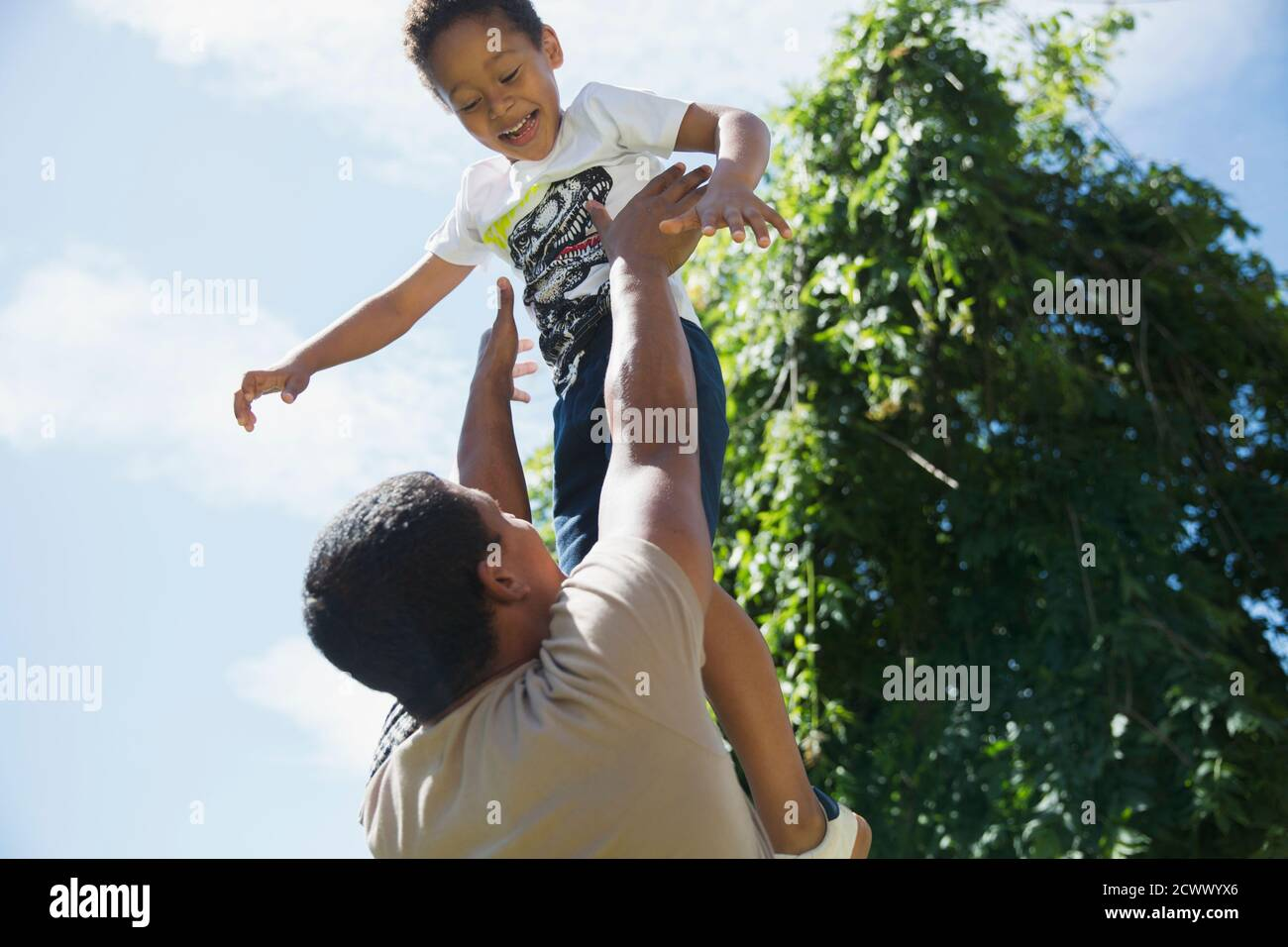 Un père qui jette son fils au soleil pour jouer Banque D'Images