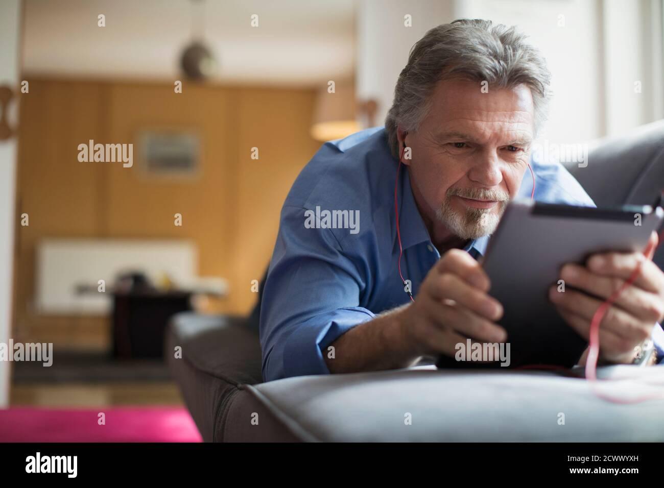 Homme senior utilisant un casque et une tablette numérique dans le salon canapé Banque D'Images
