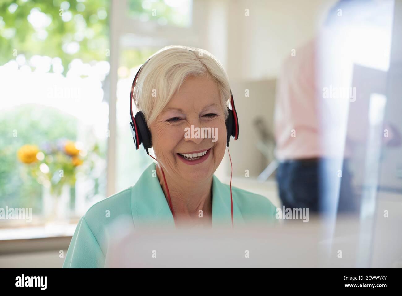 Femme âgée heureuse avec un casque utilisant un ordinateur portable dans la cuisine Banque D'Images